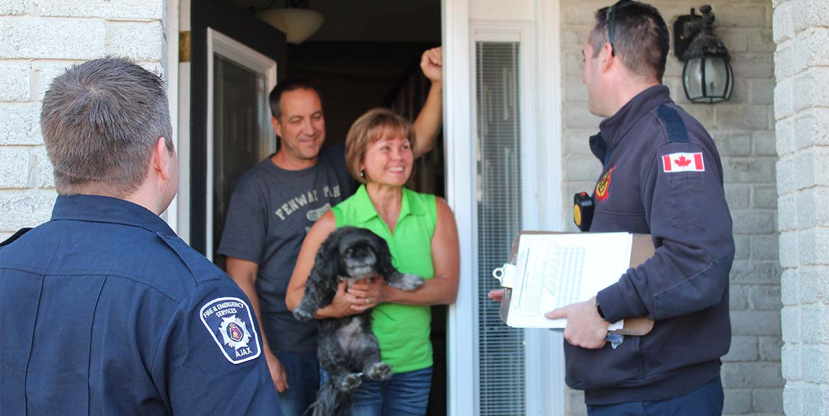 Firefighters visiting a couple at their door.